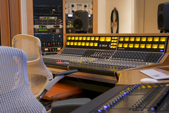 A recording studio with two chairs and a mixing console, with a rack of equipment in the background