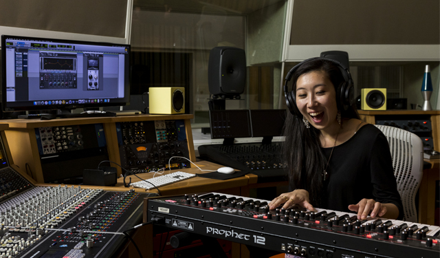 A woman in a black shirt with headphones on is playing the keyboard while sitting in a recording studio