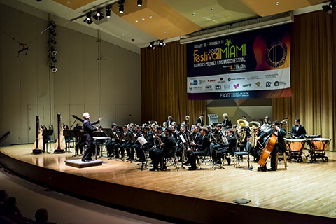 A conductor in the spotlight motions with a baton in his right hand as an orchestra dressed in suits follows his directions at the 2017 Festival Miami