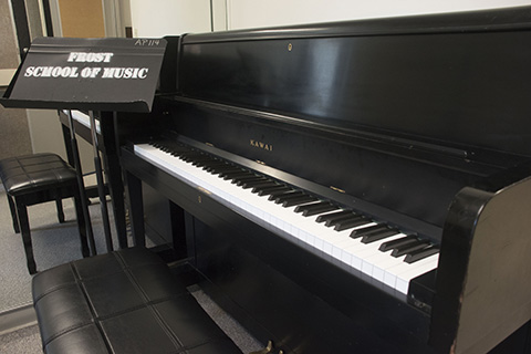 A black Kawai piano and a sheet music stand with the words Frost School of Music printed on it