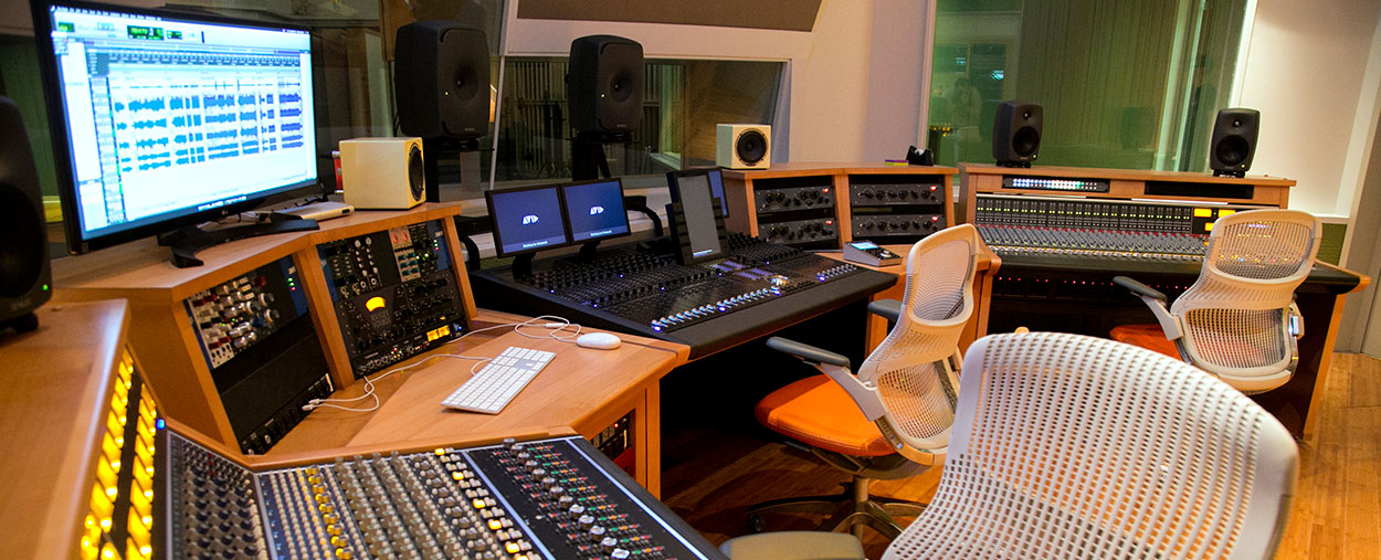 A audio engineering control room featuring computers, mixing boards, and other hardware